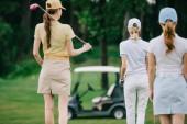 zadní pohled na ženy s golfové vybavení na zeleném trávníku na golfovém hřišti