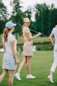 vista parziale delle donne in protezioni con attrezzatura da golf, camminare sul prato verde, presso campo da golf