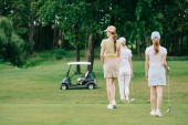 back view of women with golf gear walking on green lawn at golf course