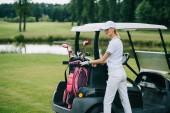 Žena v polo a čepici s golf zařízení stojící u golfový vozík na golfovém hřišti v letním dni