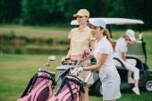 Fotografia messa a fuoco selettiva dei giocatori di golf femminile con attrezzature da golf e amico in carrello di golf dietro il prato verde