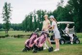 Selektivní fokus ženské golfové hráče golfové vybavení a přítel v golfovém vozíku za na zeleném trávníku