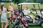 ženské golfové hráče v caps na golfový vozík na golfovém hřišti