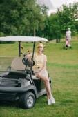 Fotografia fuoco selettivo del giocatore di golf femminile al carrello di golf sul prato verde
