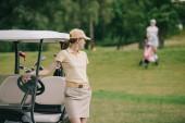 Fotografie Selektivní fokus ženské golfové hráče v hlavici na golfový vozík na zeleném trávníku
