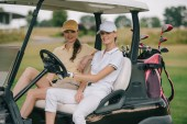 smiling women in caps sitting in golf cart and looking at camera