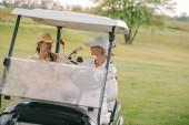usmívající se žena golfisty na koni golfový vozík na golfovém hřišti