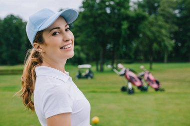 side view of smiling woman in polo and cap looking at camera at golf course