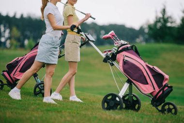 partial view of female golf players in polos walking on golf course