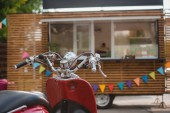 close-up view of red scooter and food truck behind