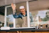 cheerful young man waving hand and smiling at camera while working in food truck