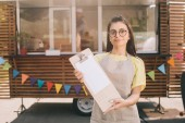 beautiful young woman in apron and eyeglasses holding blank clipboard and smiling at camera while standing near food truck