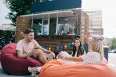 Fotografie happy young friends talking while sitting on bean bag chairs near food truck