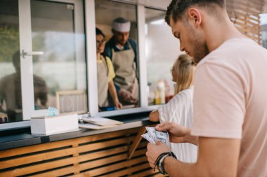 young man counting money while standing in line at food truck