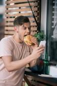 Mann isst Burger und benutzt Smartphone bei Foodtruck