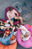 Fotografie high angle view of friends clinking with bottles of beer and holding fast food on bean bag chairs