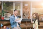 Fényképek mosolyogva chef rendelés adva a vásárlók élelmiszer-teherautó