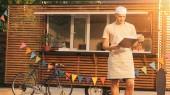 kuchař v zástěře pohledu na schránky u kamionu potravin