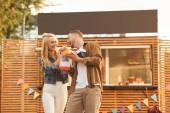 Fotografie girlfriend feeding boyfriend with burger near food truck