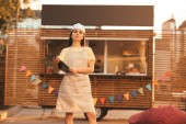 Fotografie beautiful chef in apron holding clipboard near food truck and looking at camera