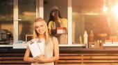 Fotografie atraktivní usměvaví kuchaři s menu při pohledu na fotoaparát u kamionu potravin