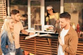 Fotografie customer grimacing and rejecting burger from chef in food truck