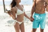 Fotografie oříznutý pohled páru s kokosovým koktejly, drželi se za ruce na pláži