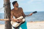 Fotografie mužské shirtless hudebník, hrál na akustickou kytaru na pláži