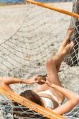 fiatal nő a bikini gazdaságot, kókusz koktél és függőágyban fekvő beach