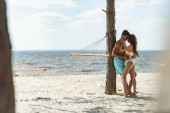 Fotografie couple of tourists embracing on beach with hammock near the sea
