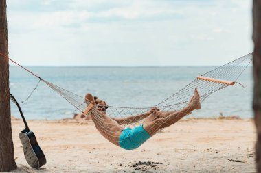 handsome bearded man lying in hammock on beach near the sea