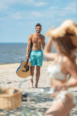 handsome man with acoustic guitar and girl on bicycle on seashore, selective focus