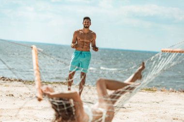 handsome shirtless man bringing coconut cocktails to his girlfriend on hammock near the sea