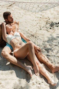 Happy beautiful couple lying on sandy beach stock vector