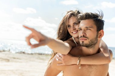 man piggybacking his girlfriend, while she pointing on beach