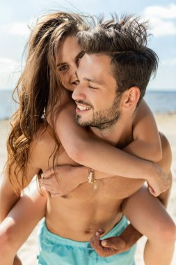 happy beautiful couple piggybacking on beach near the sea