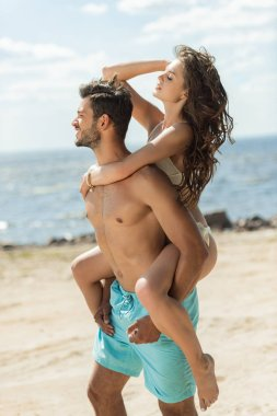 handsome boyfriend piggybacking his beautiful girlfriend on sandy beach near the sea