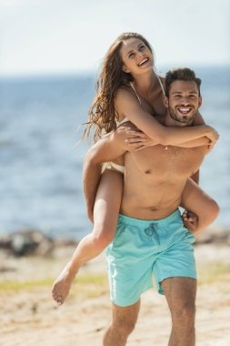 cheerful man piggybacking his smiling girlfriend on seashore
