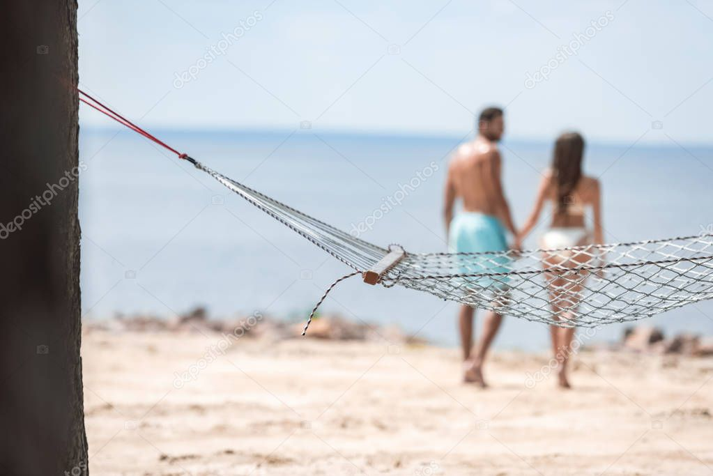 selective focus of couple holding hands and walking on beach with hammock on foreground