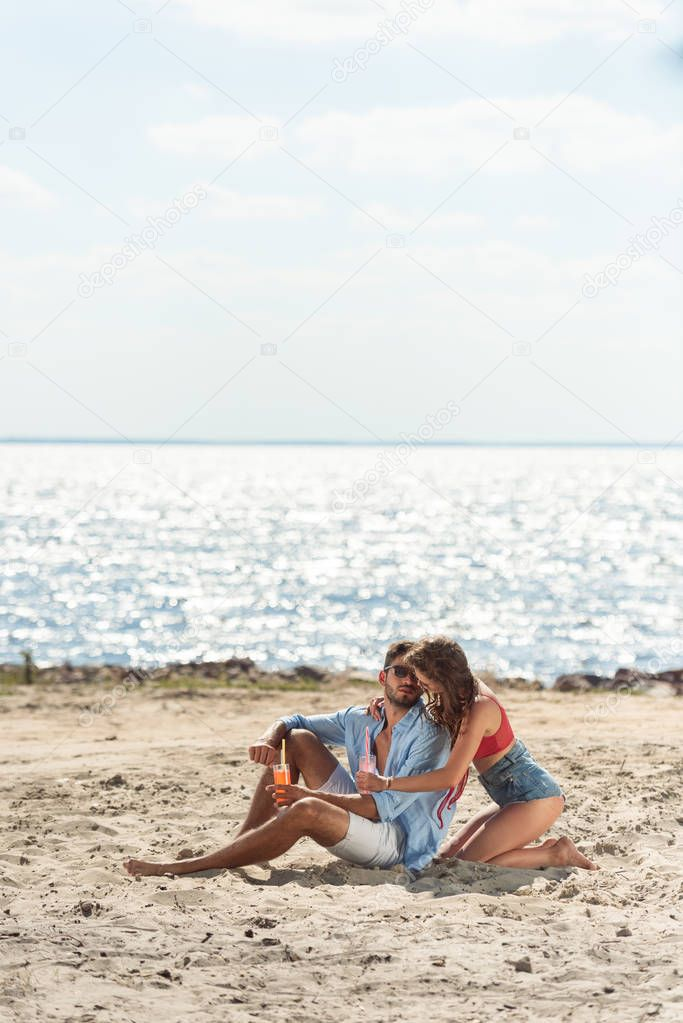 couple with cocktails sitting on beach near the sea