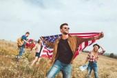 hübscher junger Mann Usa Flagge- und Wanderwege durch Feld mit Freunden während der Reise
