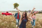 glückliche junge Frau hält Blumenstrauß in der Hand und geht mit Freunden auf dem Feld spazieren