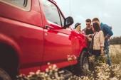 Gruppe junger Freunde Auto-Reiseplanung mit Landkarte auf Motorhaube