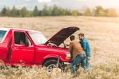 hezký mladí muži při pohledu na rozbité auto motor v poli