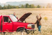 young men standing near car with broken engine in field and waving at camera
