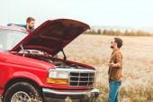 Fotografie mladí muži stojící poblíž auto s nefunkční motor v poli