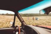 Blick vom Auto am Gruppe junger Leute, die vorbeikamen Blumenfeld während der Autofahrt