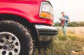 közeli felvétel piros teherautó állt a mező homályos ember, Térkép a háttérben navigáció