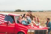 Gruppe der jungen amerikanischen Auto fahrenden entspannend in Blumenfeld