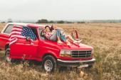 beautiful young girlfriends relaxing on car hood in field